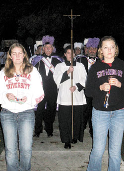 Indiana University students Alicia Munchel, 20, left, and Kayleen Glaser, 19, take part in the eucharistic procession on the Bloomington campus on Oct. 14. Members of the Knights of Columbus also were among those who took part. Despite the rain and cold weather, nearly 100 people participated in the prayerful gathering. (Photo by Kamilla Benko)