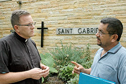 """Rolando Mendoza Sr. makes a point about the need for immigration reform in the United States to Father Michael O'Mara, pastor of St. Gabriel the Archangel Parish in Indianapolis. The priest and the parishioner both support the Catholic Church's emphasis that """"humane"""" reform is needed. (Photo by John Shaughnessy)"""