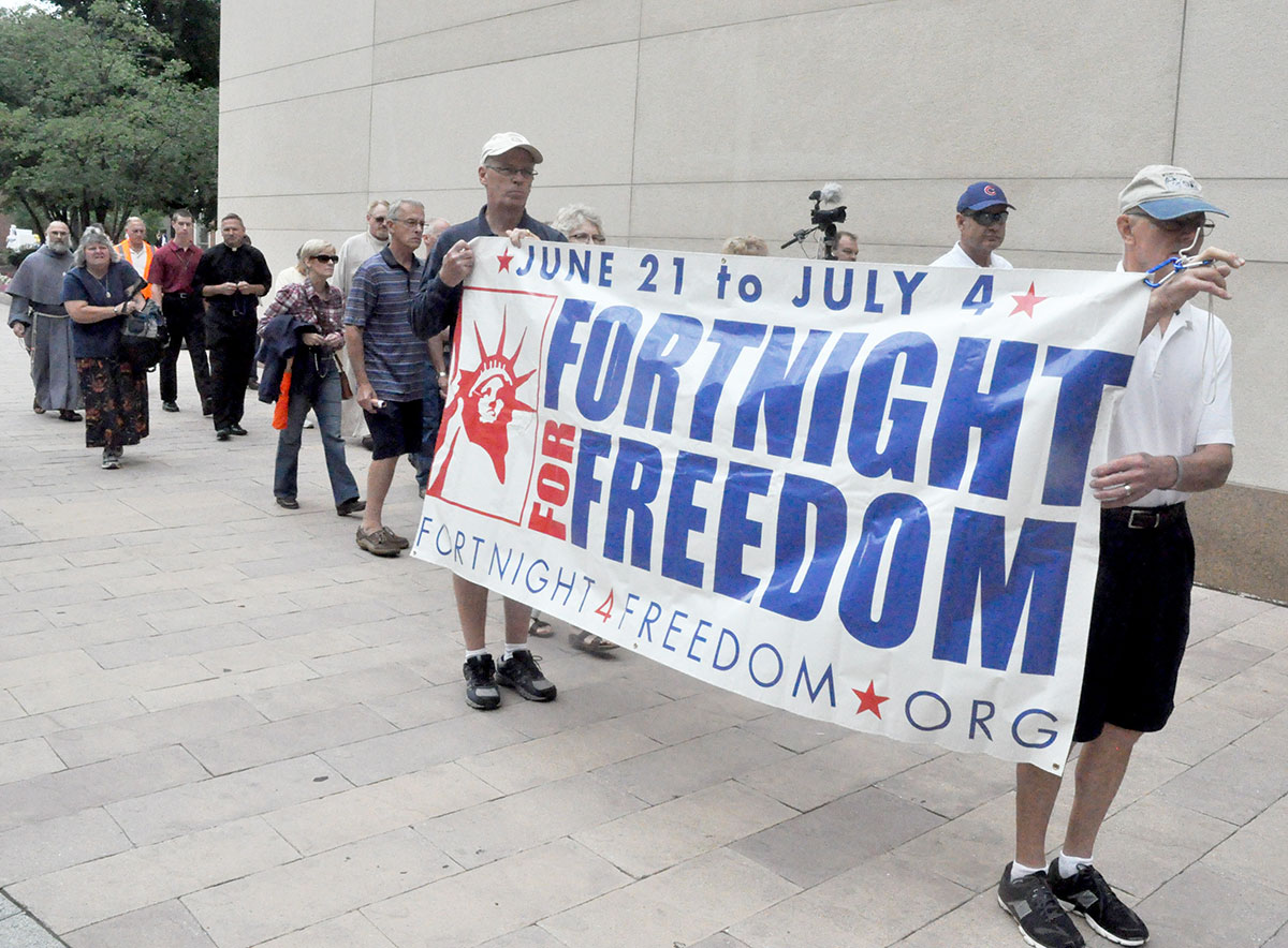 Frank oliver left and jim west carry a fortnight for freedom banner