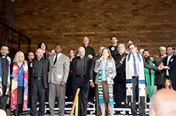 Priests and leaders of other faith congregations stand in solidarity for immigrants and refugees during an event at which Indianapolis Mayor Joe Hogsett spoke out against discriminatory practices by law enforcement against immigrants and refugees on Feb. 12 in the St. Philip Neri School gymnasium in Indianapolis. Shown in this photo are four pastors of Indianapolis parishes: Father Christopher Wadelton, pastor of St. Philip Neri Parish, third from left; Father Todd Goodson, pastor of St. Monica Parish, center; Msgr. Paul Koetter, pastor of Holy Spirit Parish, behind Father Goodson; and Father Rick Ginther, pastor of Our Lady of Lourdes Parish, second from right. (Submitted photo by IndyCAN)