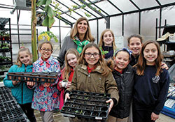 Members of the horticulture club at St. Bartholomew School in Columbus pose for a photo with principal Helen Heckman in the school's greenhouse-outdoor learning lab in early March. (Photo by John Shaughnessy)