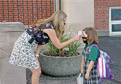 Assistant principal Kortney Wenclewicz checks the temperature of first-grade pupil Maddy Weber on Aug. 20, the first day of classes at Christ the King School in Indianapolis. (Photo by John Shaughnessy)